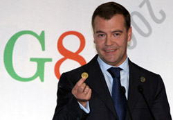 President Dmitry Medvedev showing reporters a sample gold coin of a possible global currency at the G8 summit in L'Aquila, Italy, on Friday. Mikhail Klimentyev / RIA-Novosti / AP