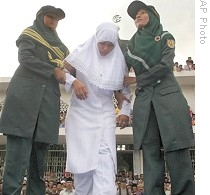 Shariah officials bring Acehnese woman onto stage for caning as part of implementation of Islamic Shariah law, outside mosque in Banda Aceh, (2006 file photo)