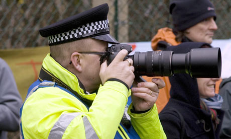 policeman takes photographs of CND protesters